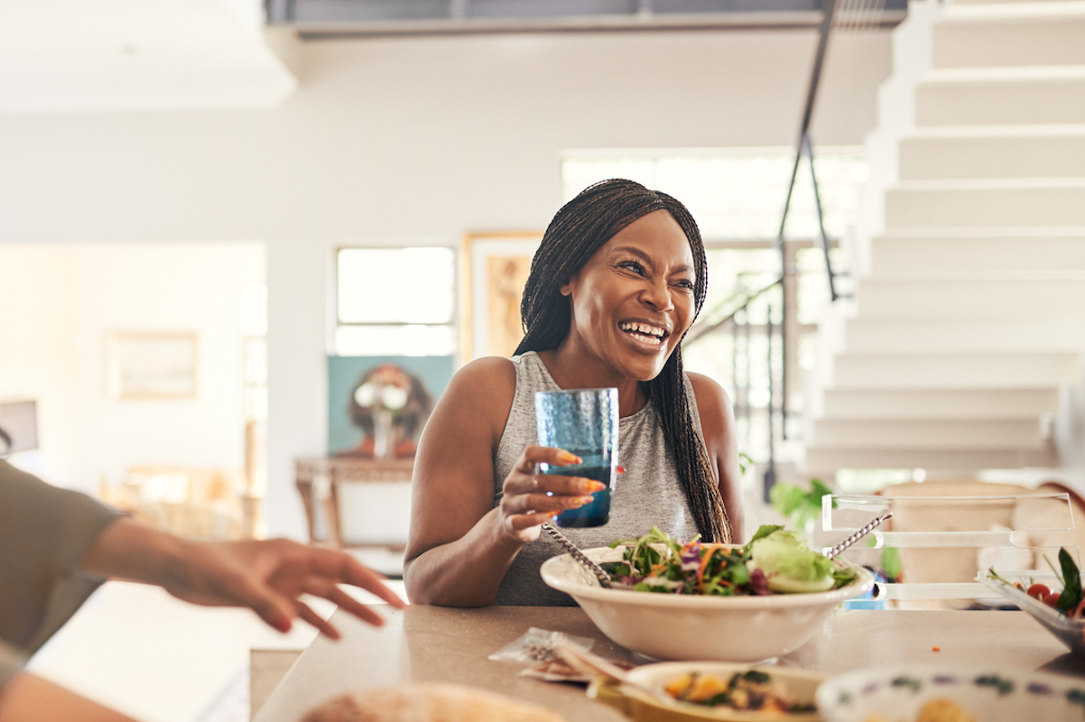black woman having lunch with family in the kitchen at home, drinking diet soda and eating salad