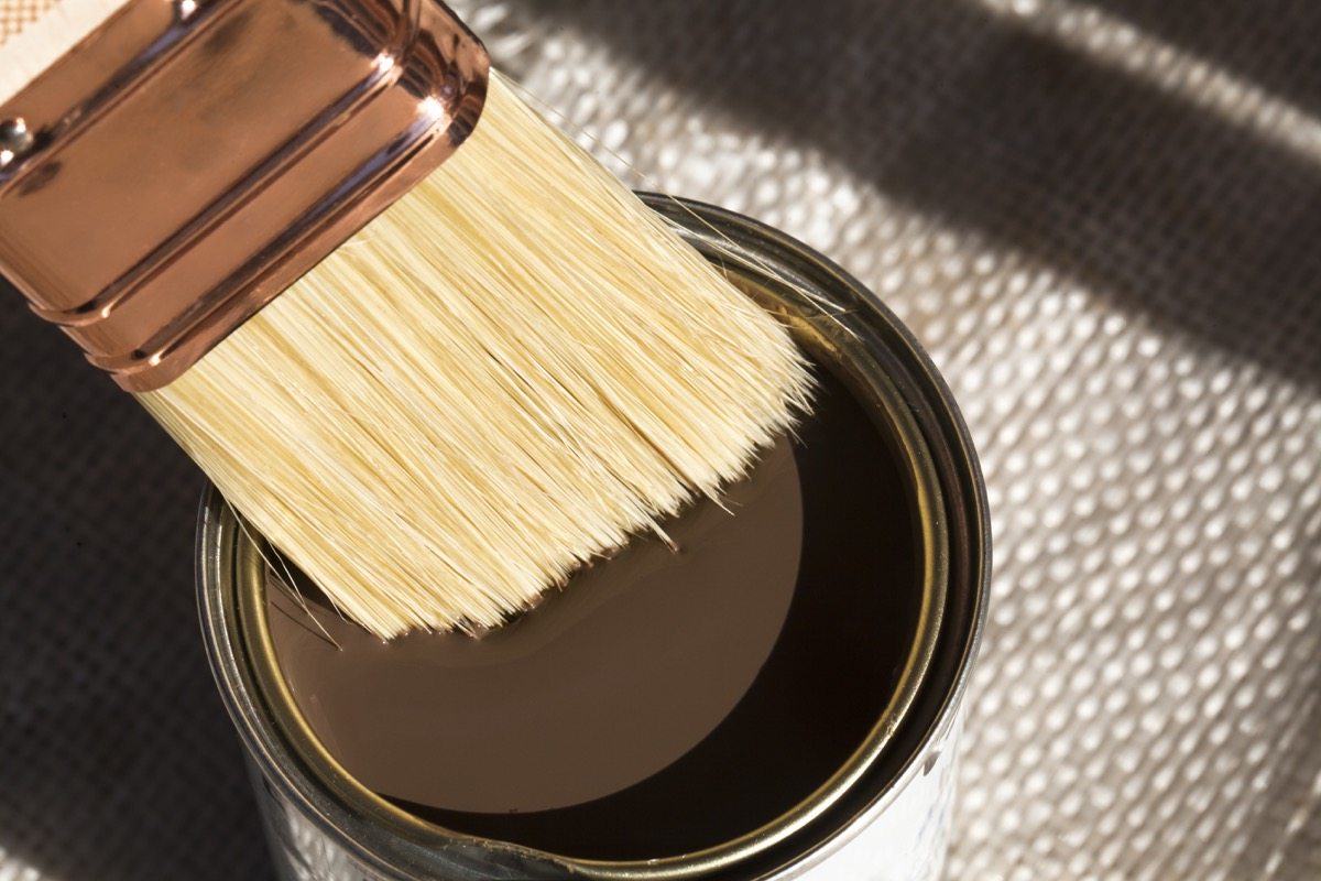close up of a can of brown paint and a brush dipping into it