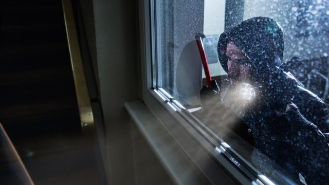 white male burglar holding crowbar and wearing hoodie peering through window of house