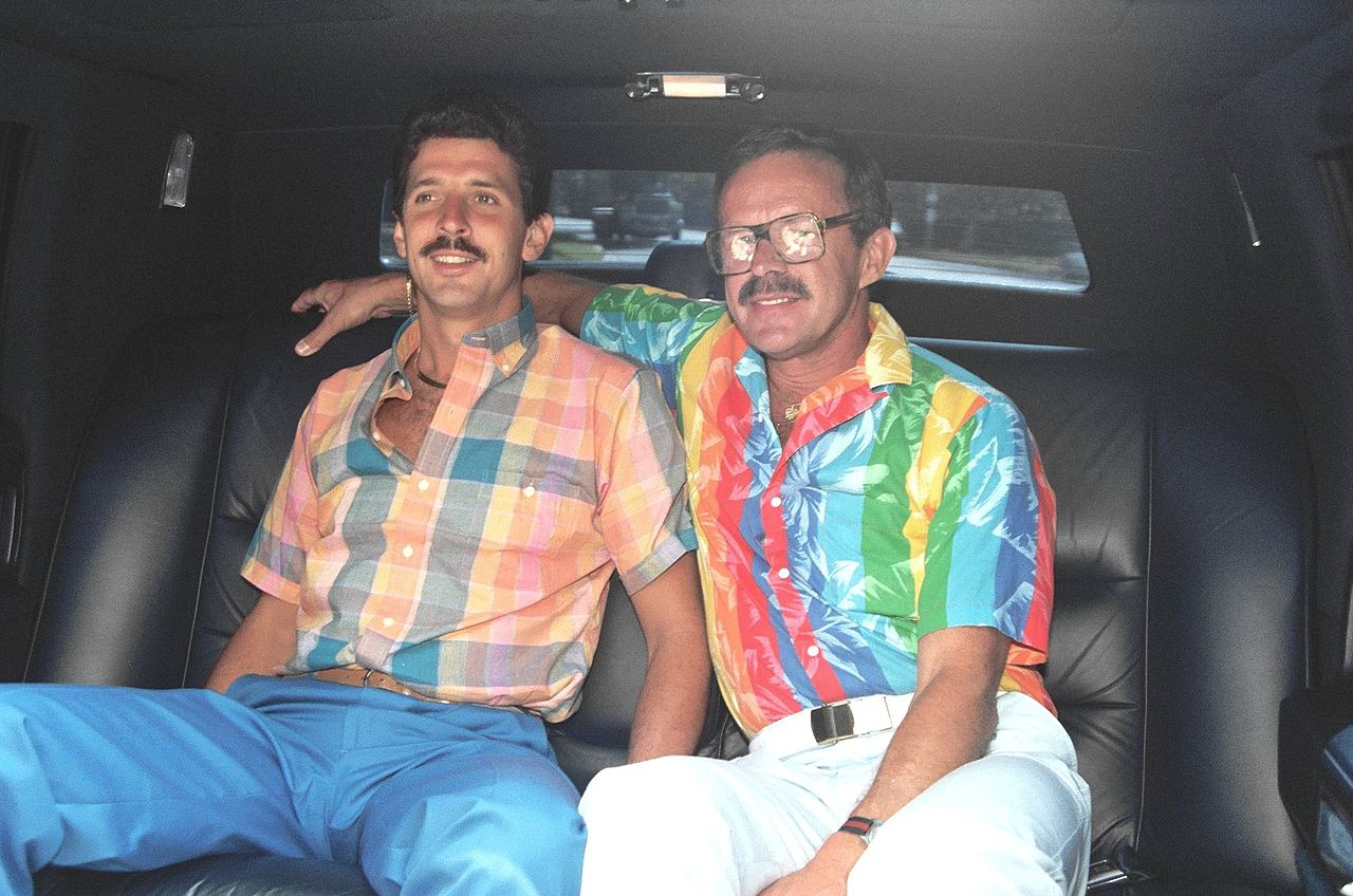 two men in the back of the car, one wearing cazal glasses, 1980s fashion