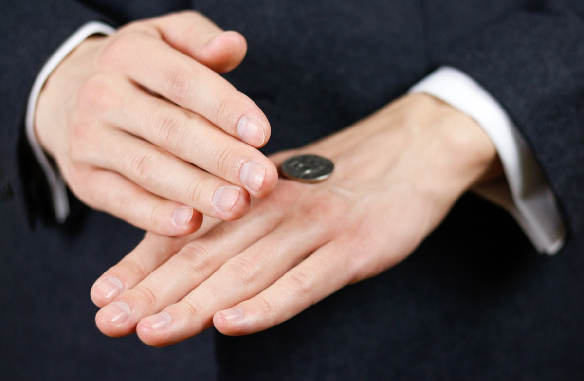 man uncovering a coin toss on his hands, terrible decisions