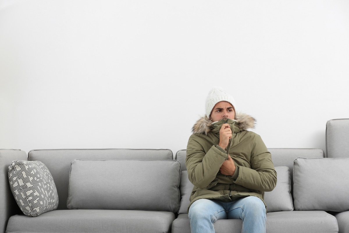 Man freezing in his living room wearing a jacket