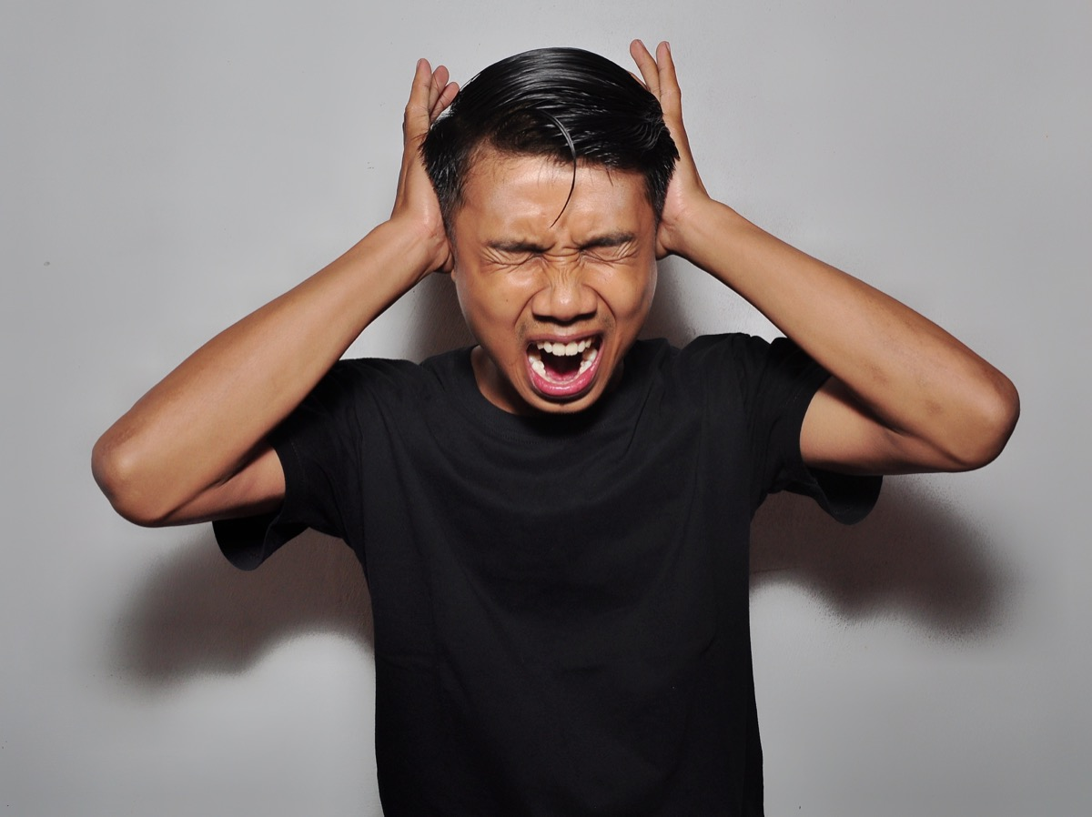 Man covering ears from noise