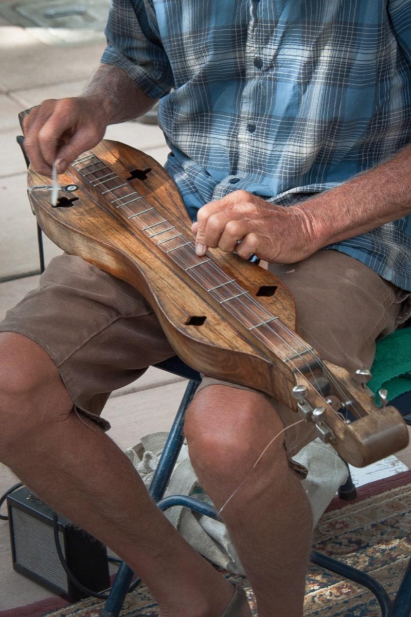 man playing dulcimer instrument, hard state facts