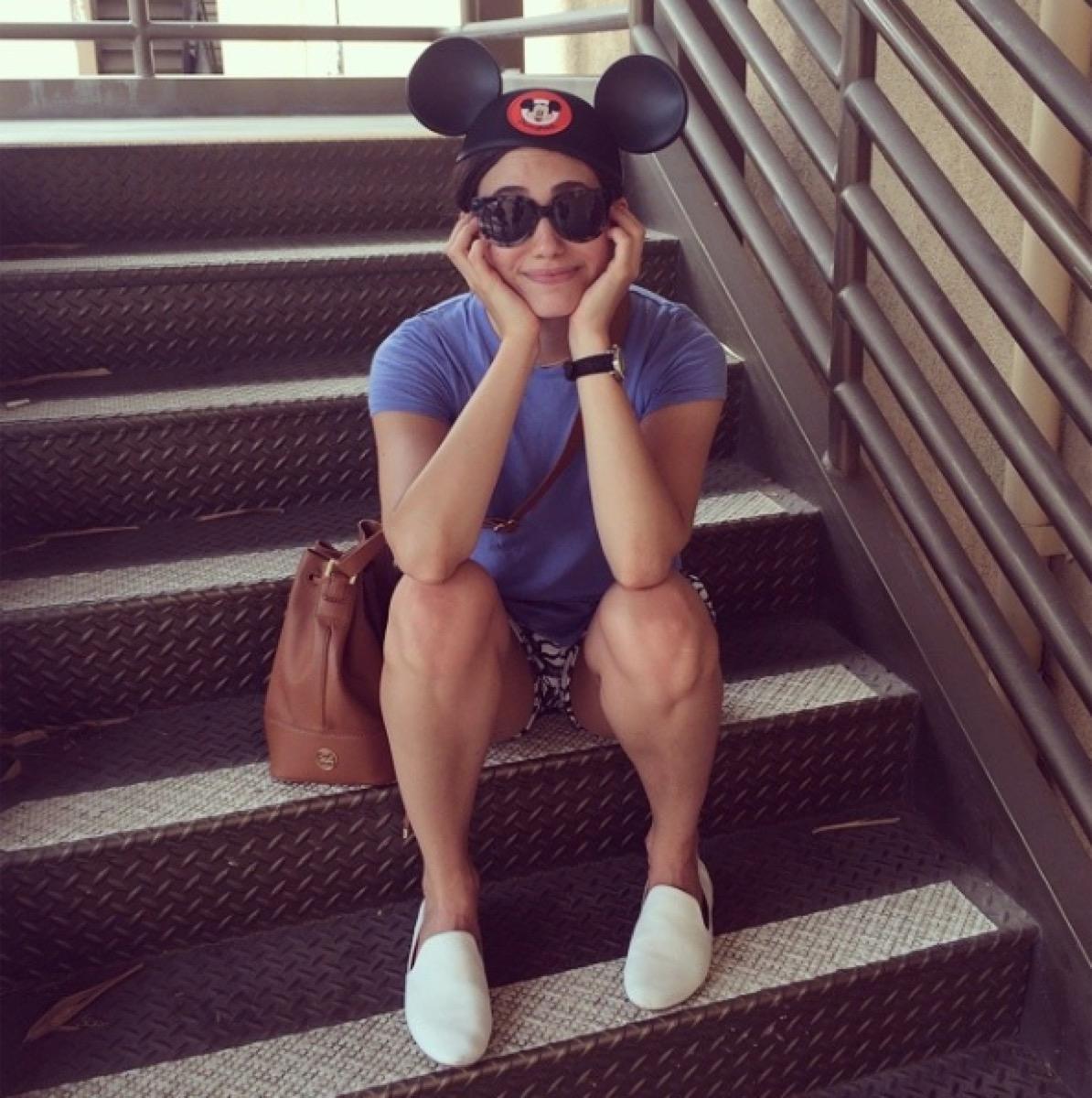 emmy rossum sitting on stairs wearing disney hat