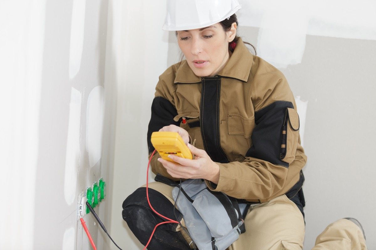 woman wearing hard hat checking an outlet for power