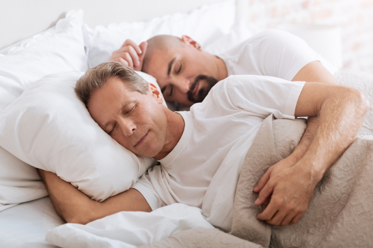 middle age gay couple spoons in bed