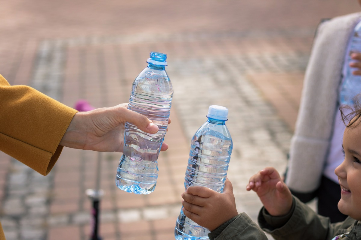 Close up of mother and daughter toasting with water bottles.