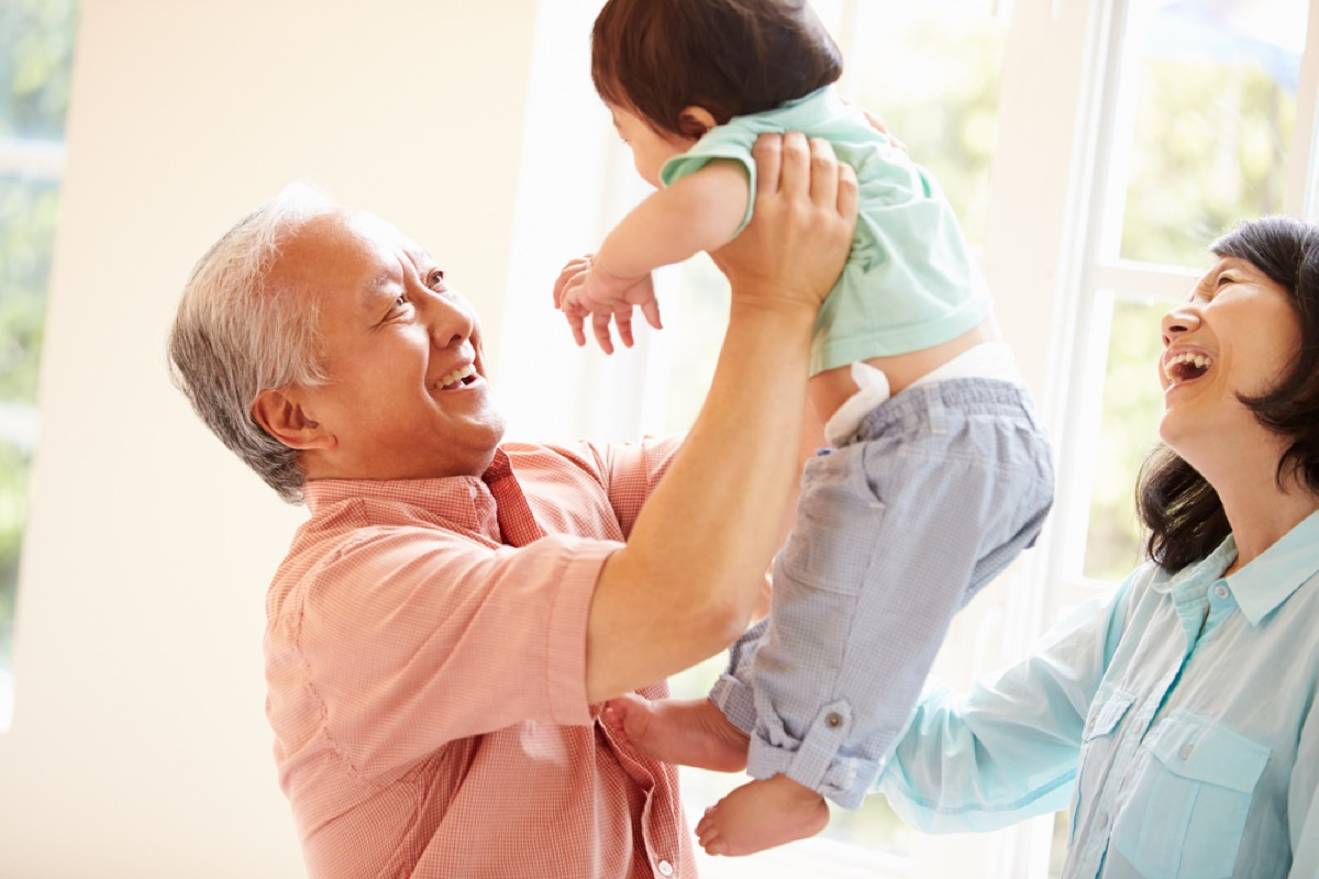 grandfather holding grandchild while grandmother looks on, things grandparents should never do