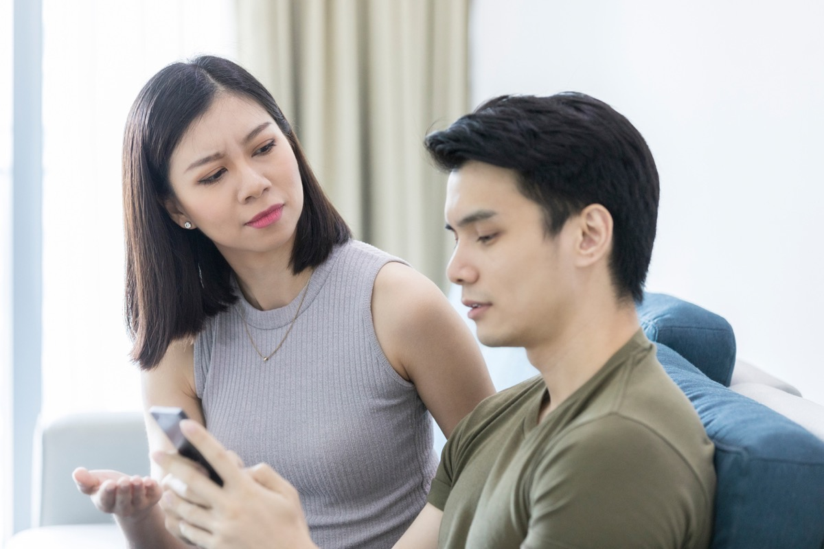 asian woman looking annoyed while asian man ignores her to look at phone