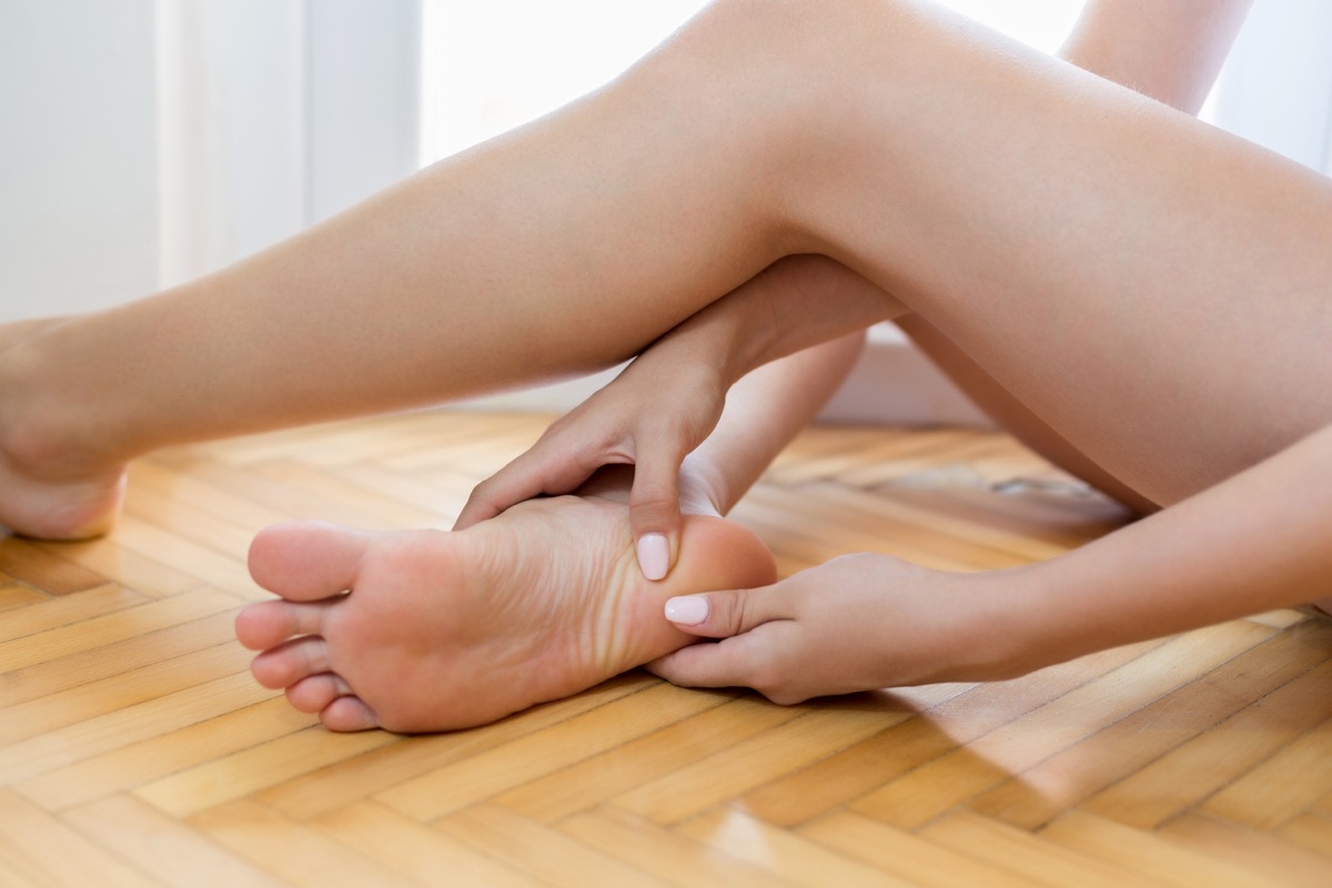 close up of white woman rubbing heel of bare feet