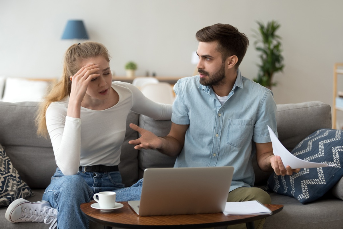 white woman with her hand on her forehead and white man putting his arms out while they hold papers and look at a laptop