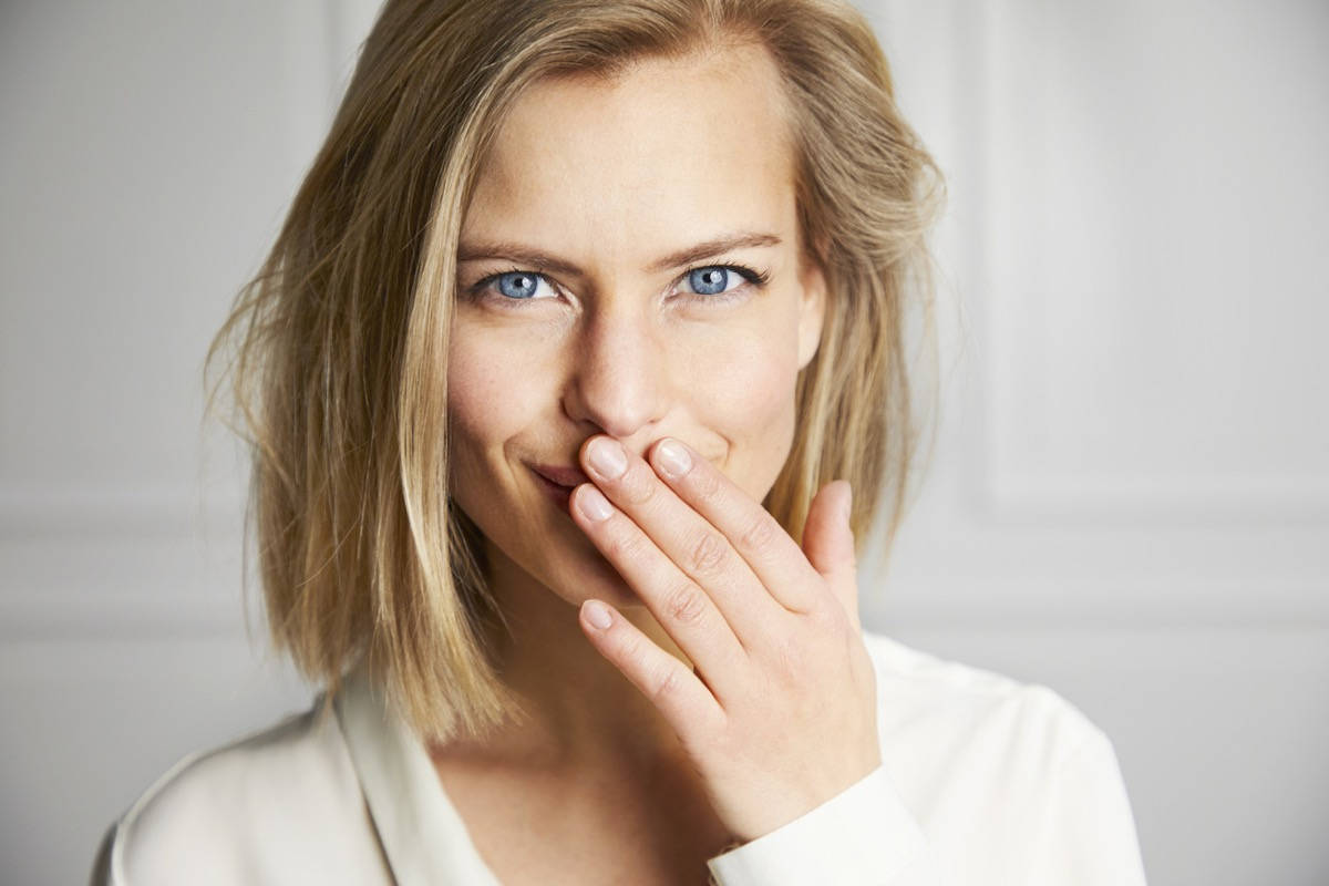 white blonde woman covering her mouth and smirking