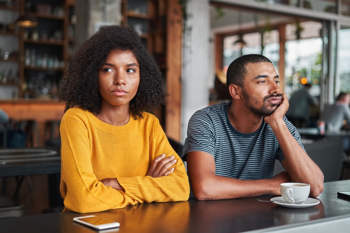 young black couple sitting next to each other at a coffee shop and not speaking or making eye contact