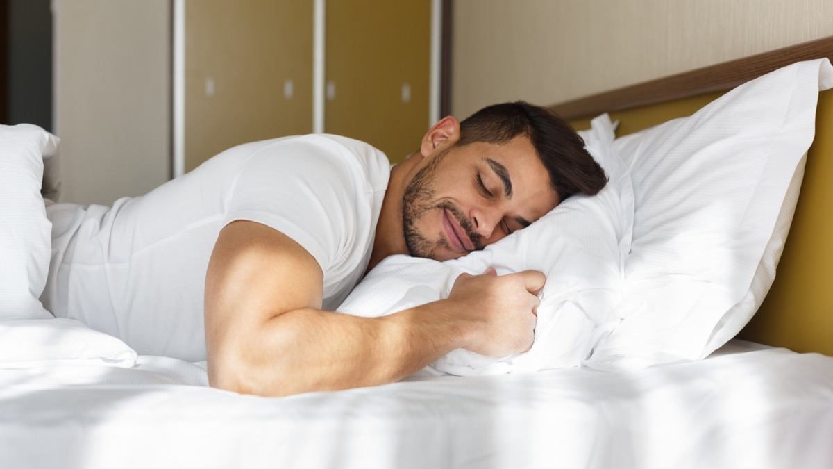 young latino man smiling with his eyes closed while lying on his pillow in bed