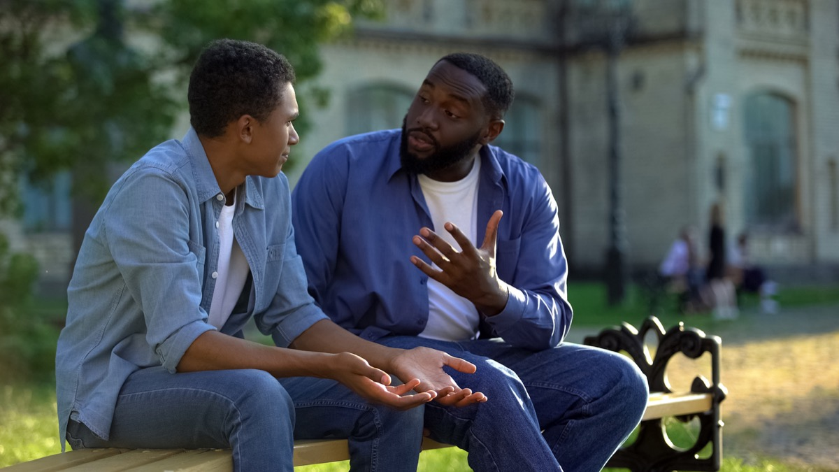 black father arguing with black son on bench outside