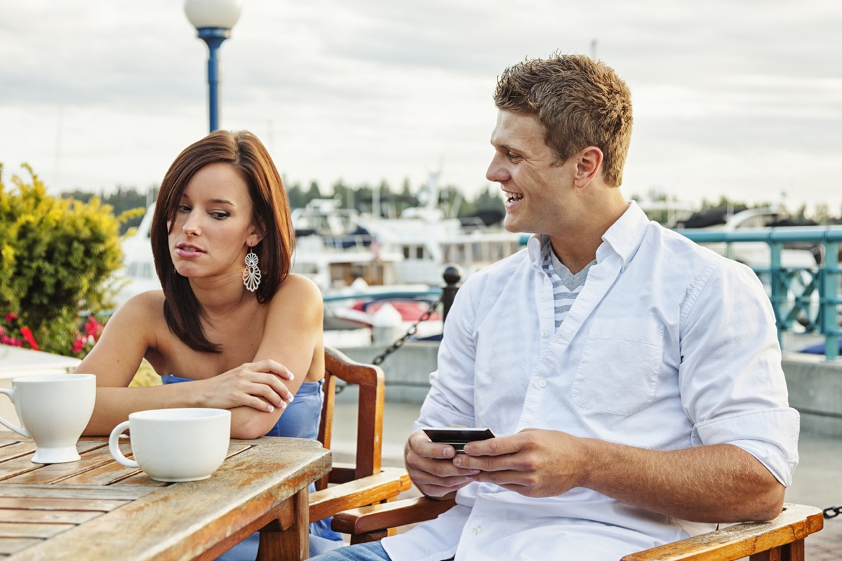 white woman looking offended by white boyfriend talking and smiling at her while sitting outside