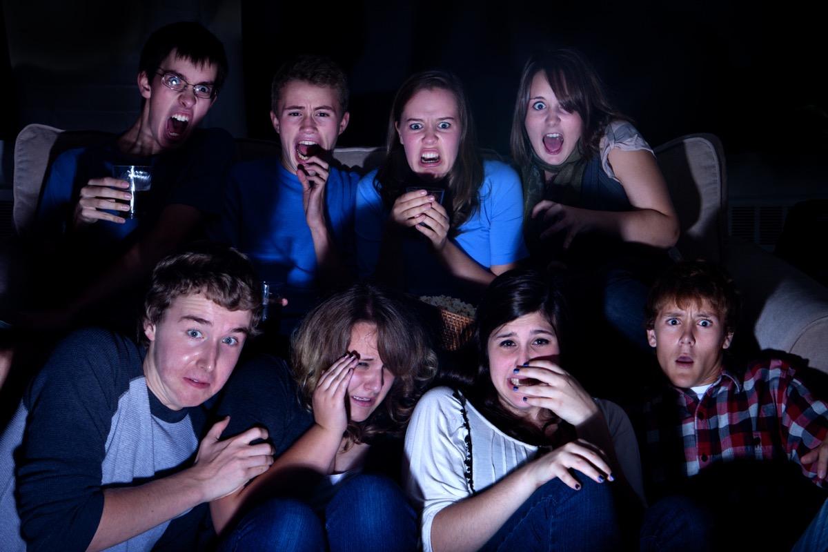 teen friends watching something shocking on tv in the dark