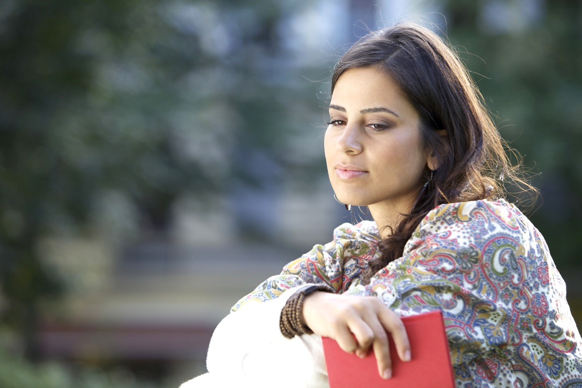 middle eastern woman looking pensive while holding a journal
