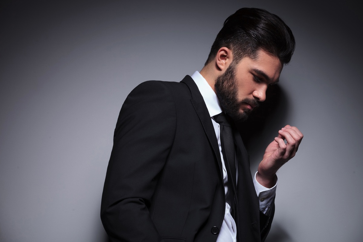 young man in suit looking at his fingernails