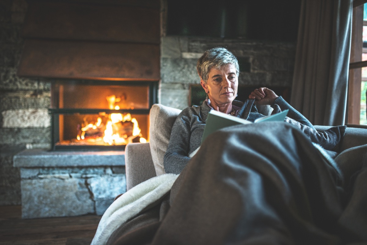 older white woman reading a book under a blanket by the fire