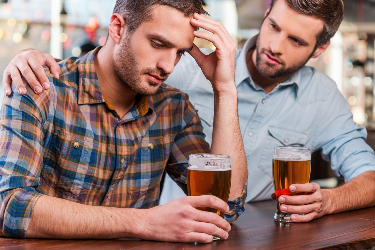 white man putting his arm around other white man while they drink beers