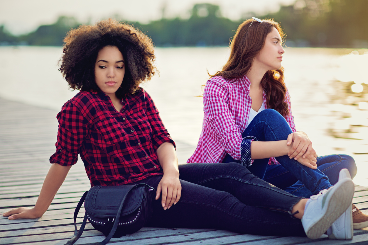 sad young black woman and young white woman sitting on the dock at a lake and not looking at each other