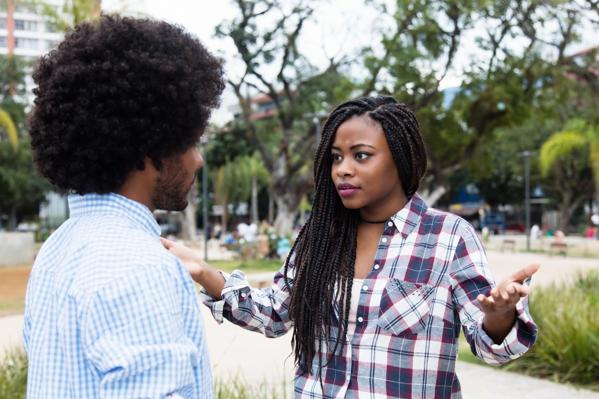 black woman throwing up hands in annoyance at black man