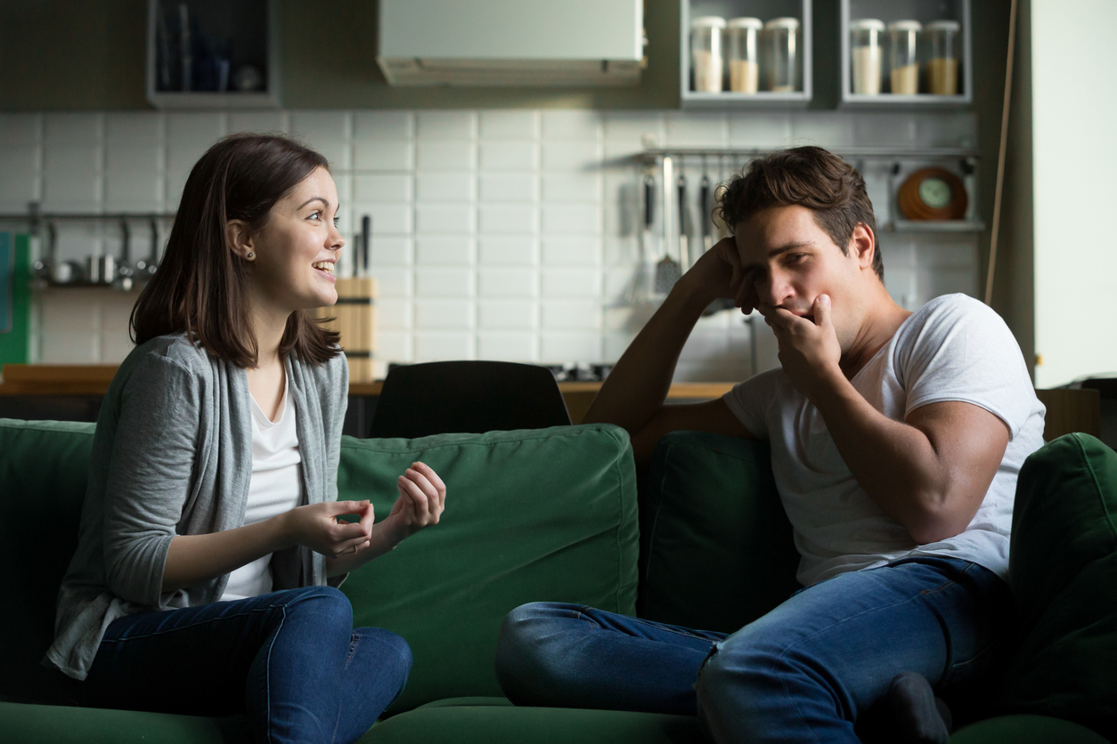 white man yawning while excited white woman talks to him on couch