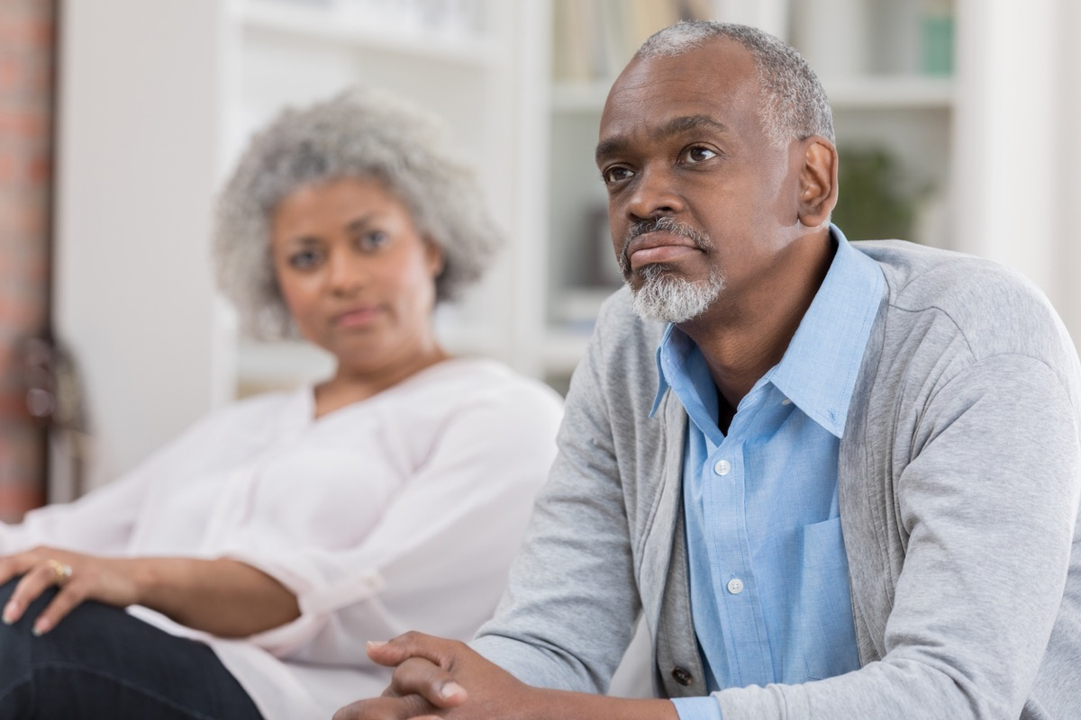 older black man sitting forward on the couch while older black woman looks at home