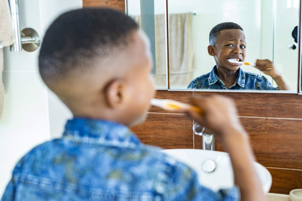 young kid brushing his teeth with toothbrush
