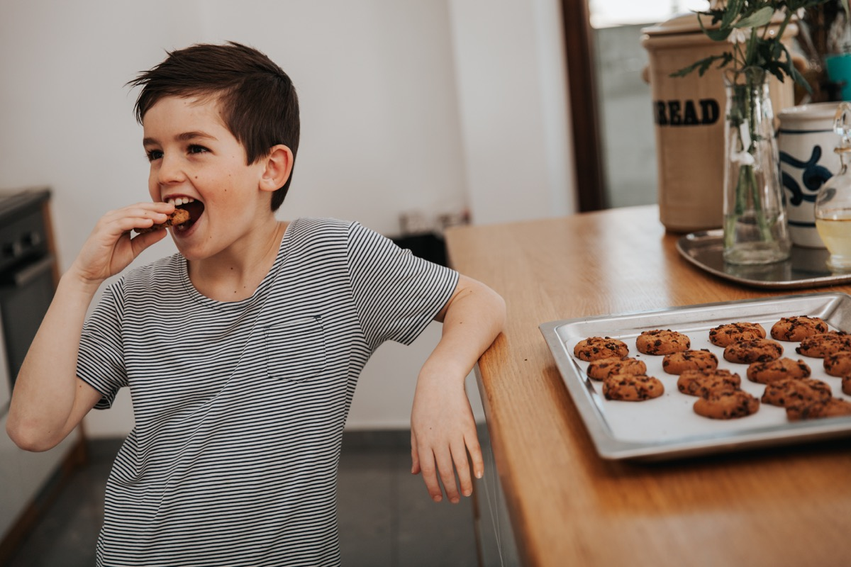 boy eating a cookie in the kitchen