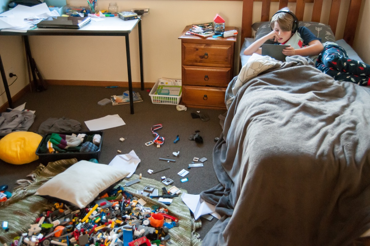 kid laying on his bed in a messy room