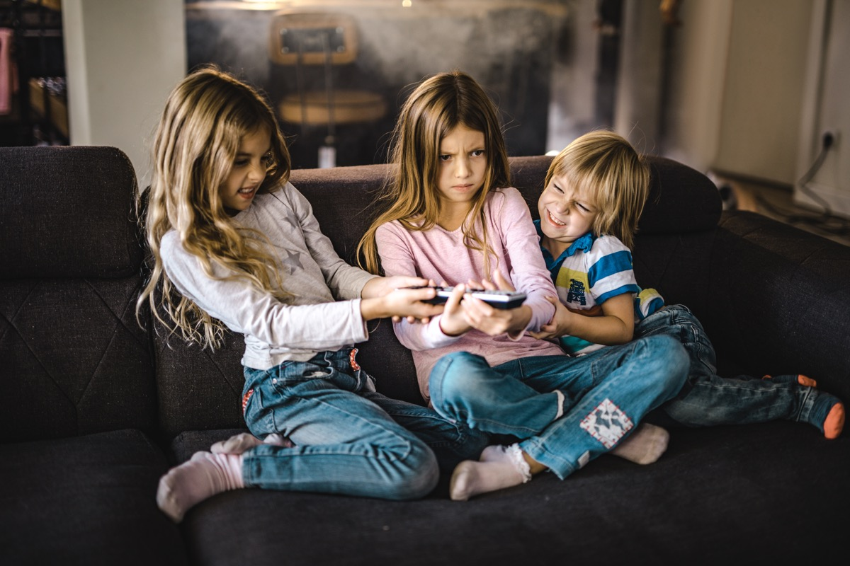 three siblings fighting over a remote