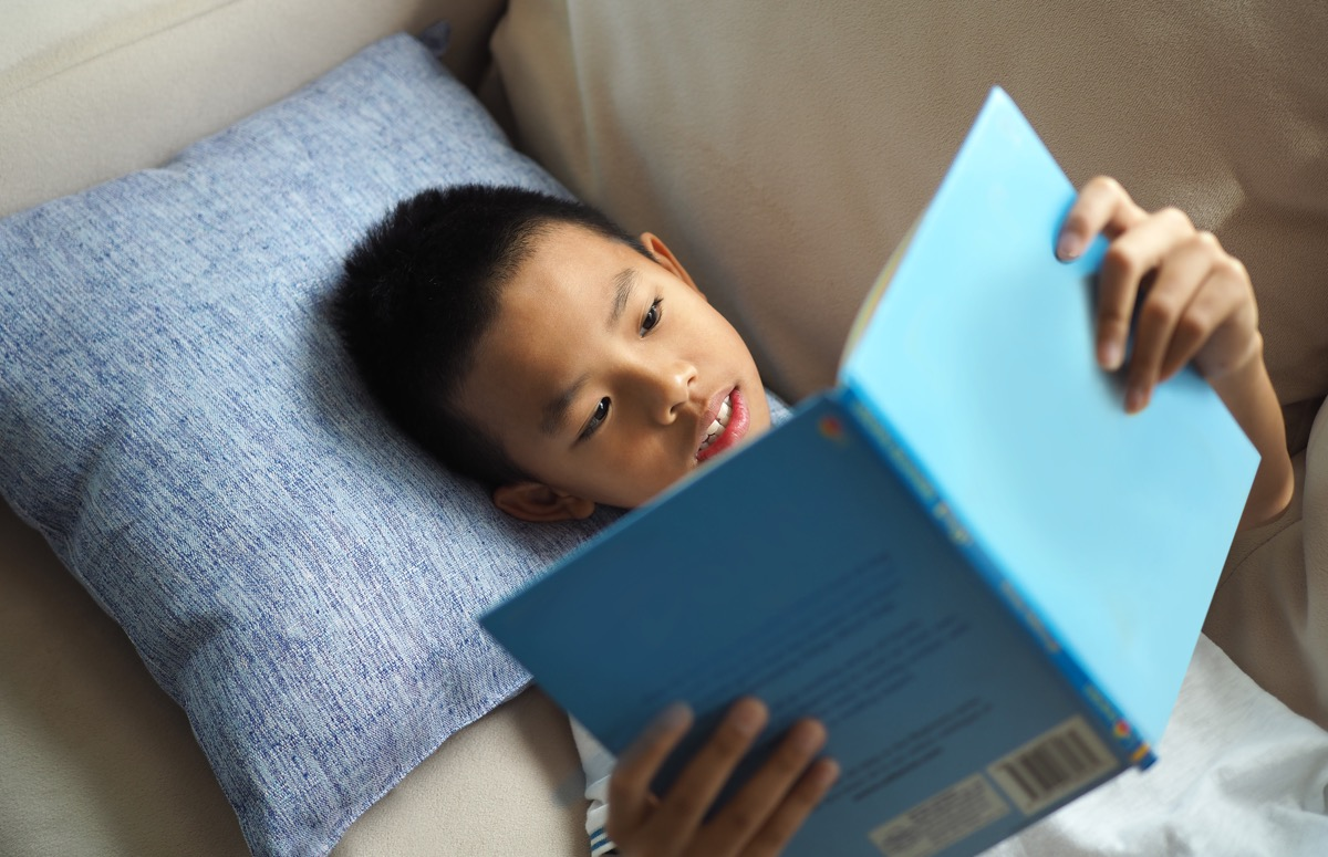 kids reading book while laying on the couch