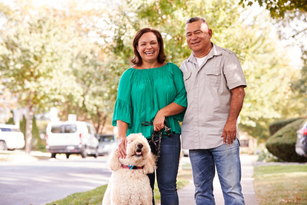 middle age latinx couple outside with dog