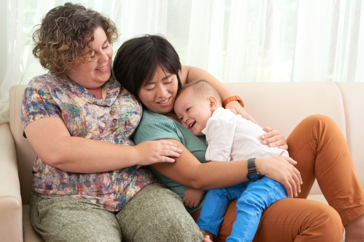 mixed race middle age lesbian couple sits on couch with baby