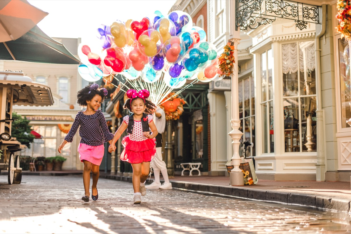 two girls with mickey mouse ears carry a bunch of balloons