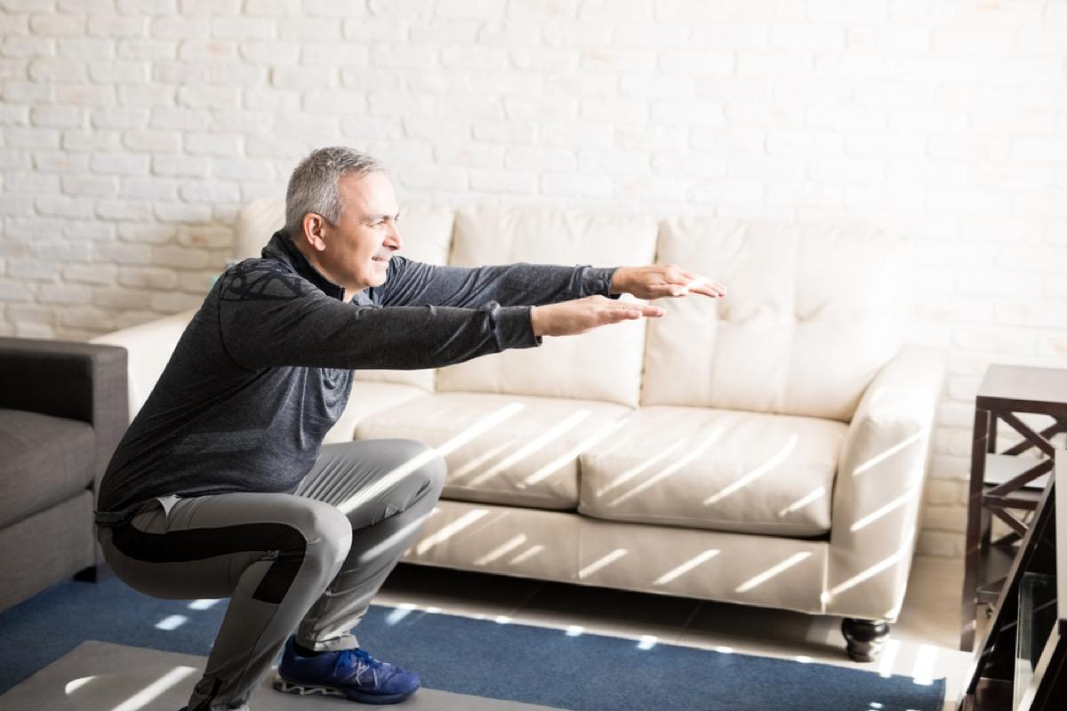 older man doing squats, health changes after 40