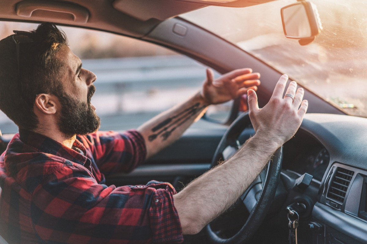 Side view image of irritated man shouting at other drivers while driving on the highway