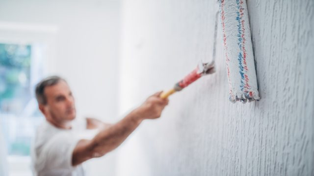 man painting walls in his home with a paint roller