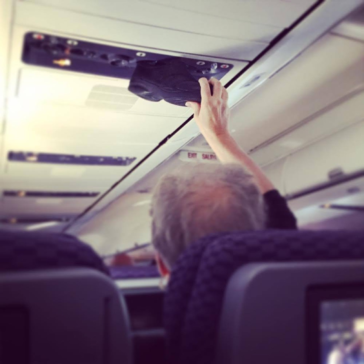 Man putting shoes to vent photos of terrible airplane passengers