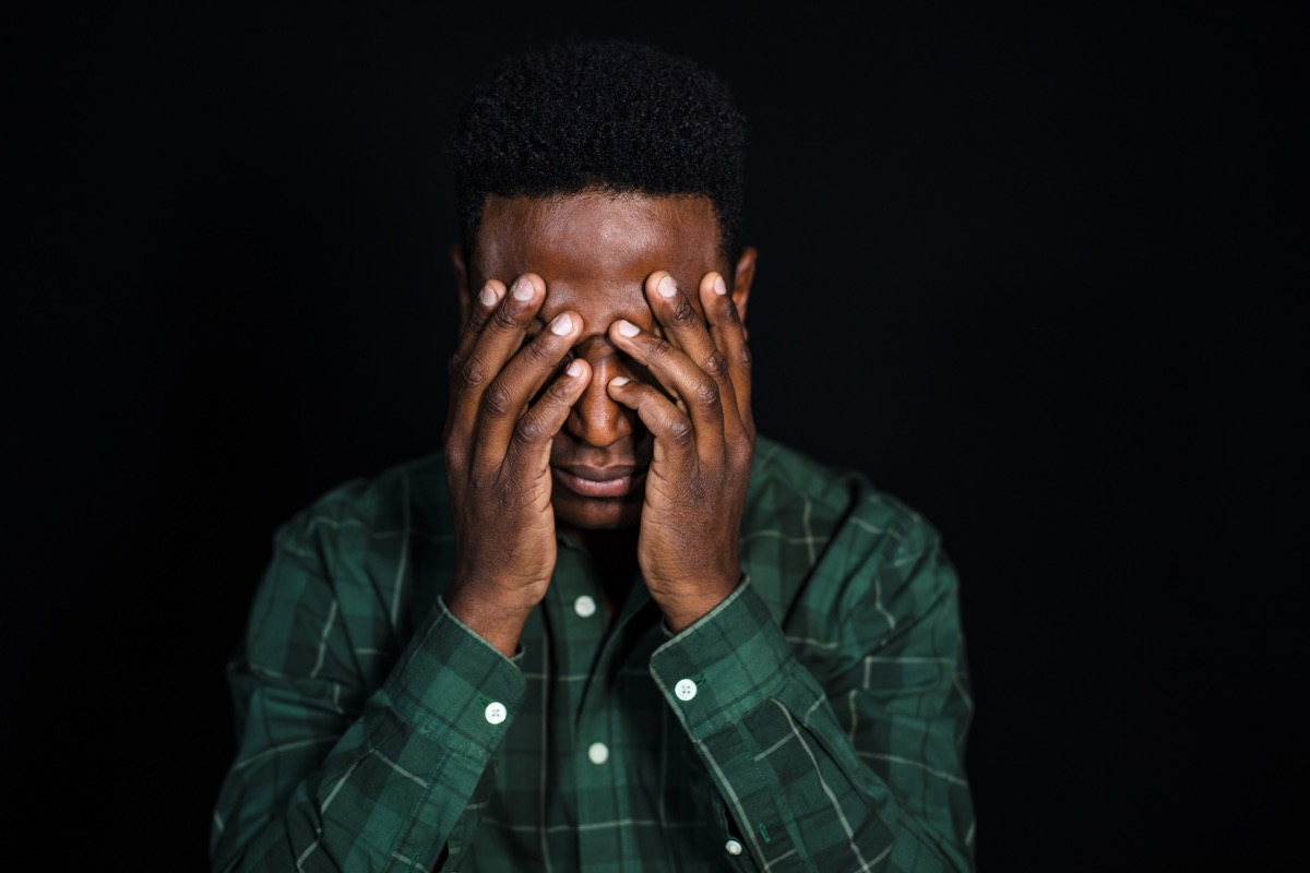 Portrait of black man with hand covering face and thinking. Male in checkered shirt looking worried on black background.