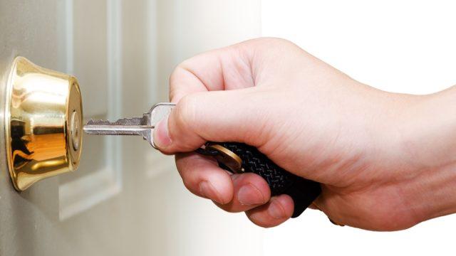 white hand unlocking door
