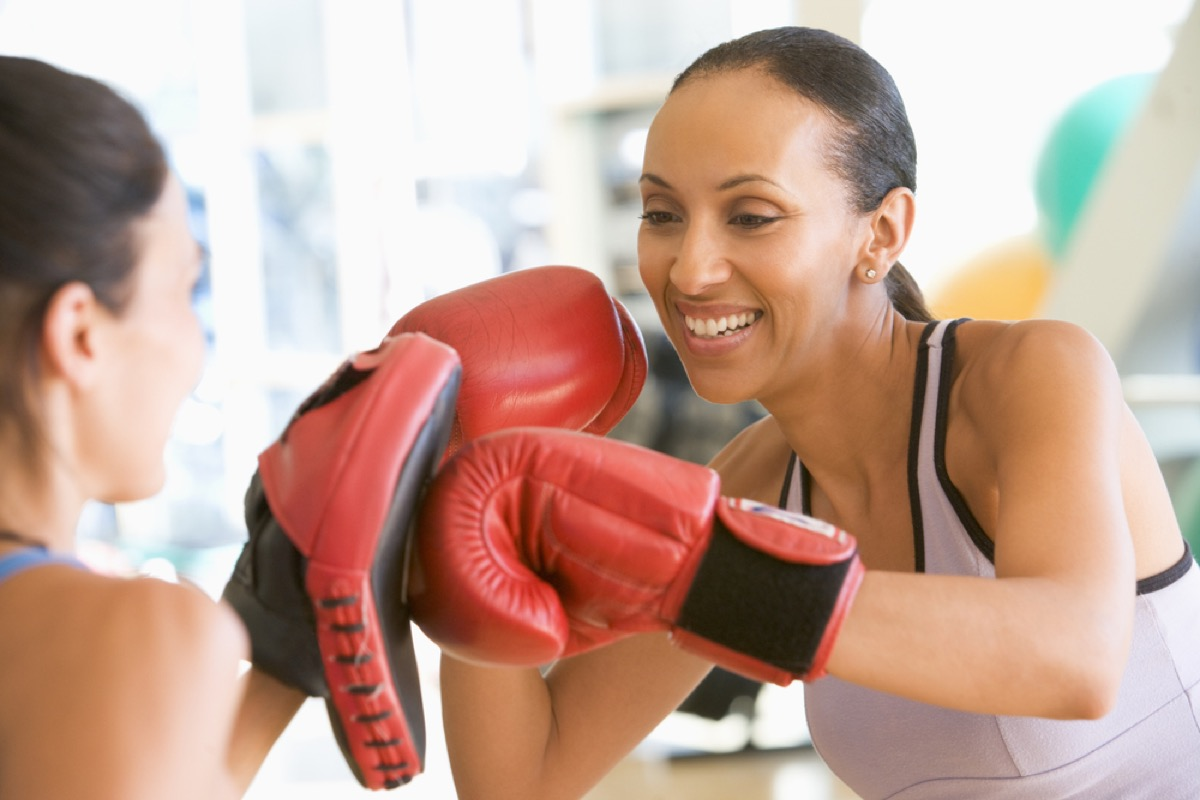 middle aged black woman smiles while sparring with boxing partner at gym