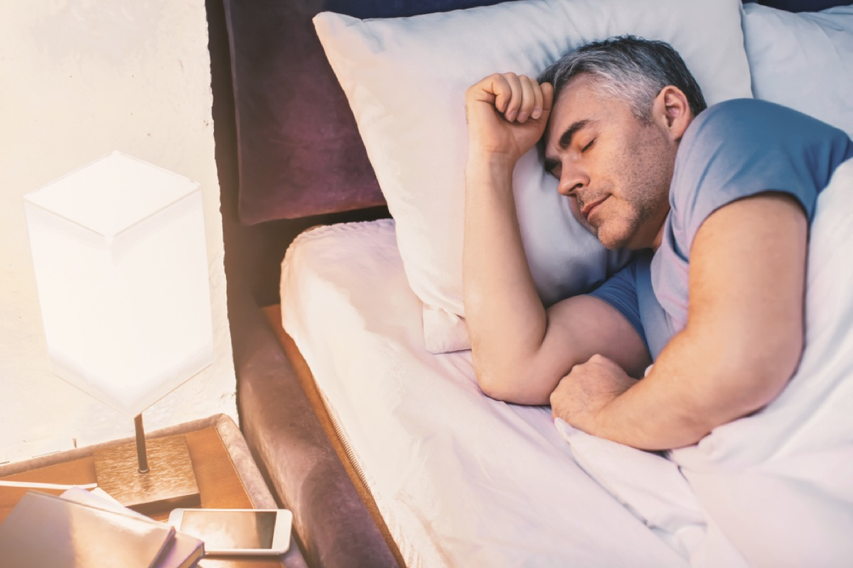middle aged white man sleeping in blue t-shirt next to lamp