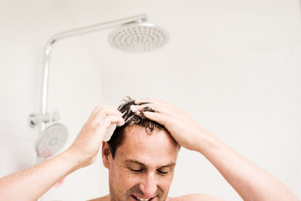 middle aged man soaps up hair in shower