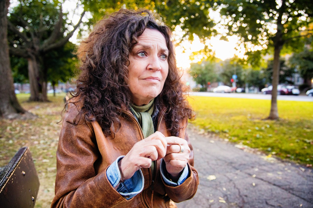 Anxious middle aged woman in crisis outdoors in park on an outdoors afternoon