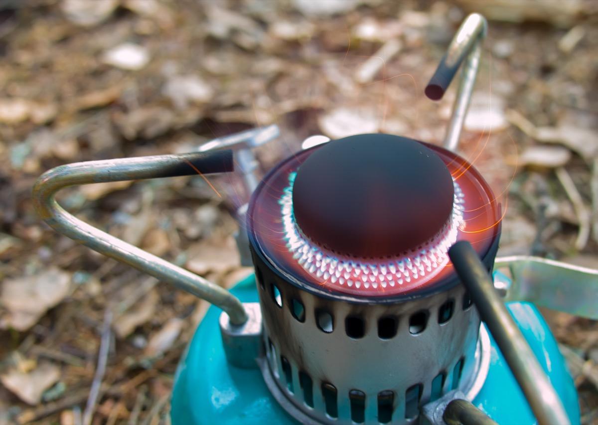 green kerosene lamp or camping stove in woods