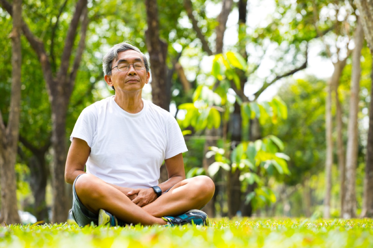 old asian man meditating and practicing meditation in park